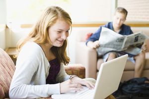 young woman on laptop and young man reading newspaper