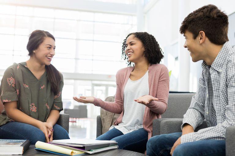 Teen friends talk in high school lobby