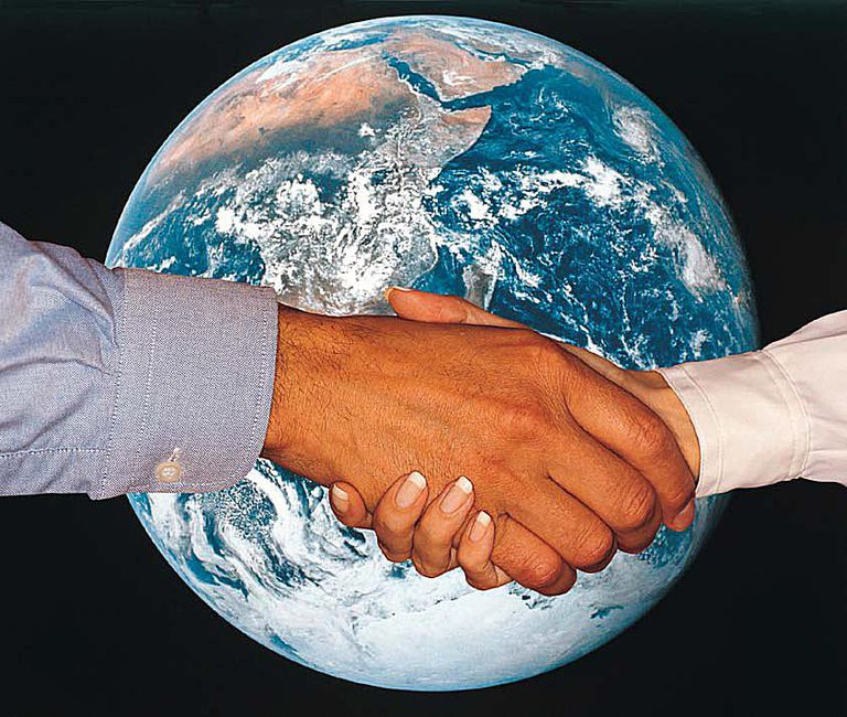 woman man shaking hands in front of photo of planet Earth