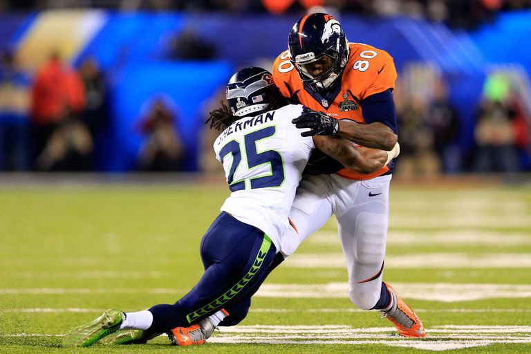Tight end Julius Thomasis tackled by cornerback Richard Sherman.