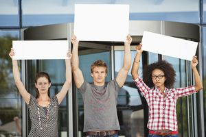 Portrait of three friends protesting with blank posters