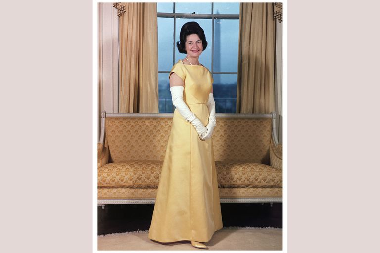 Lady Bird Johnson in a yellow gown and long white gloves, at a window - view of Washington Monument