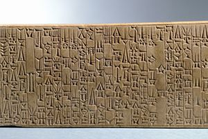 Close up of an ancient tablet against grey background.