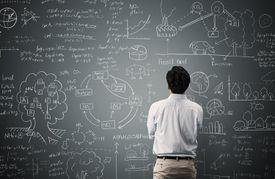 Man looking at math problem on a chalkboard.