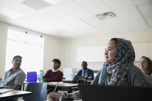 Focused ESL student in hijab listening to lesson in classroom