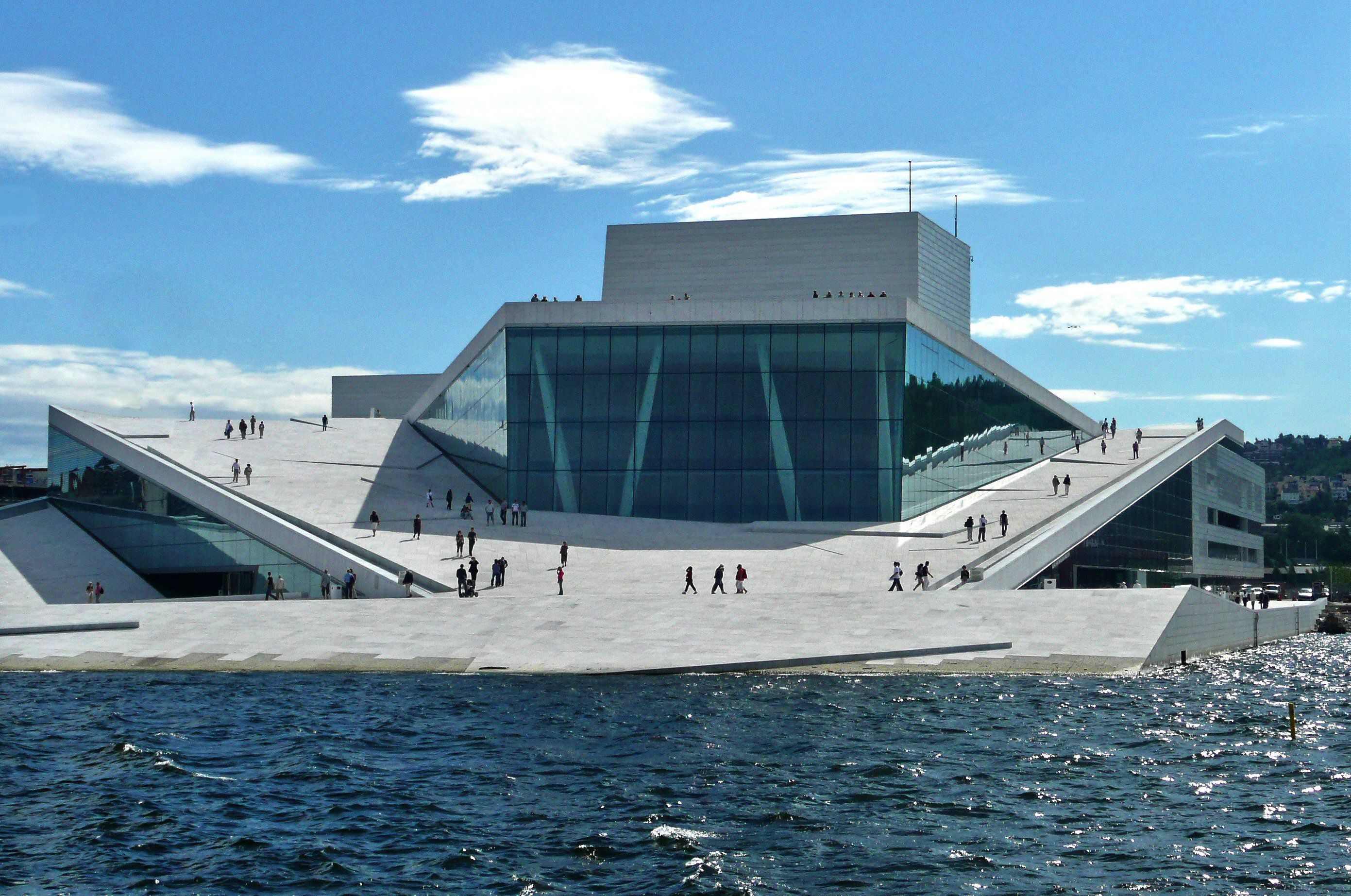 sweeping white stone ramps toward water with a sunglass-shaped building rising from the spaceport-like surroundings