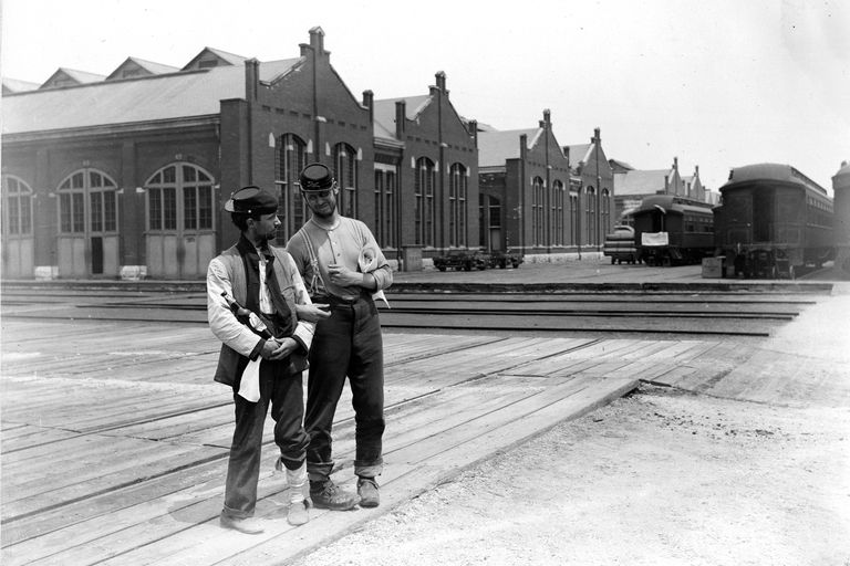 Two servicemen stand beside the Pullman Building and train cars with locked arms and a bottle of liquor during the 1894 Chicago Pullman Strike