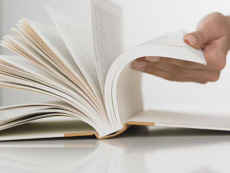 Person holding a book open.
