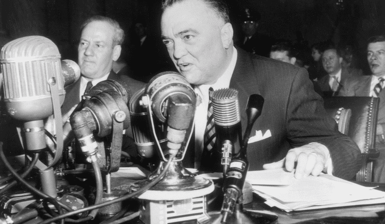 J. Edgar Hoover sitting at a table speaking before a bank of microphones.