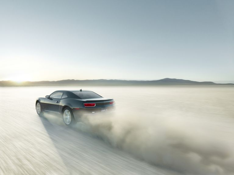 Black sports car driving on a dry lake bed