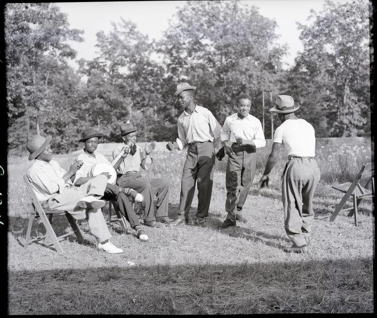 Men playing banjo and dancing