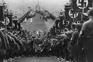 Hitler climbing stairs surrounded by Nazis with a crowd in the background