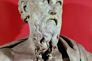 Stone bust of Hesiod against red background.