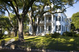 white Greek Revival style mansion, with front columns, front porches on each of the two stories, and large trees surrounding the plantation home