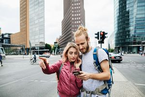 A Young Backpacking Couple in Germany pointing to a point of interest