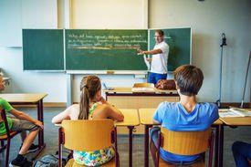 Children at desks watching a man teach class.