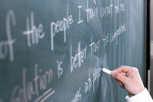 Close-up of hand writing on chalkboard