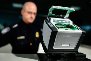 Oficial migratorio y máquina de tomar huellas digitales