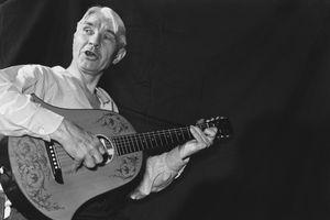 photo of Carl Sandburg playing his guitar