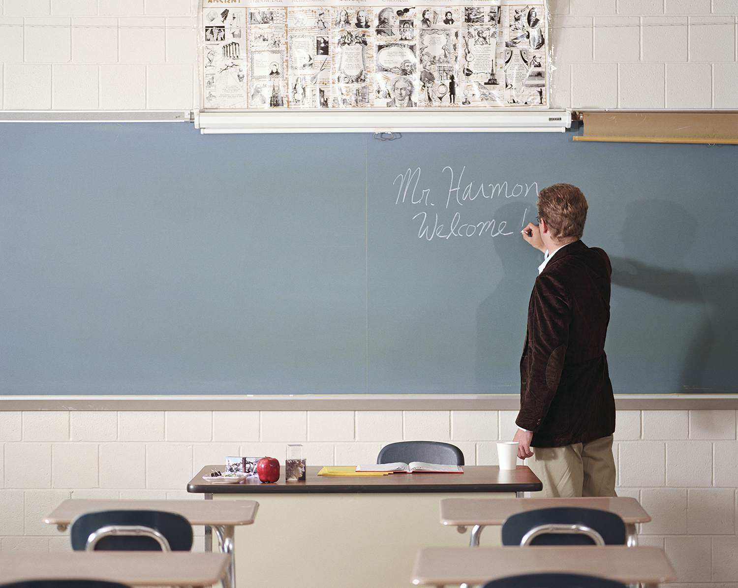 Teacher writing name on blackboard on first day of class, rear view