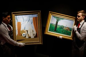 Christie's employees pose with the paintings 'Le monde poetique II' (L) and 'La belle captive' (R) by Belgian Surrealist artist Rene Magritte