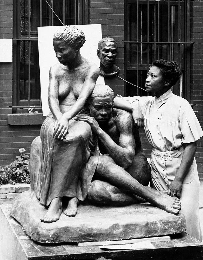 Augusta Savage posing with her sculpture