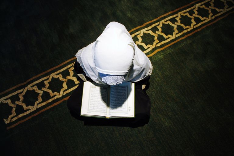 High Angle View Of Girl Wearing Hijab Reading Koran During Ramadan