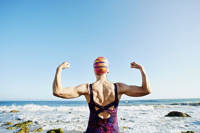 Woman swimmer flexing arms in front of ocean.