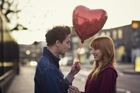 Couple walking with heart-shaped balloon