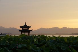 Chinese pagoda at sunset with mountains in the distance.