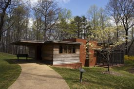 Entrance to modern wood and brick one-story house set in a wooded lot