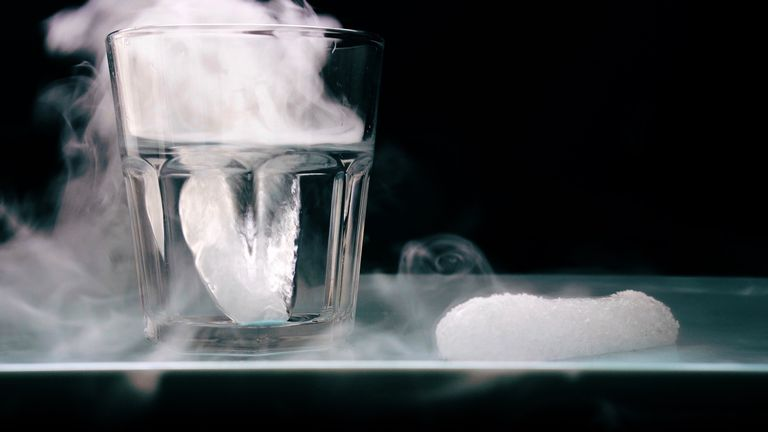 The pellet of dry ice is sublimating in air. The piece in the glass of water creates more fog because there's more contact with the water and carbon dioxide and because water has such a high heat capacity.