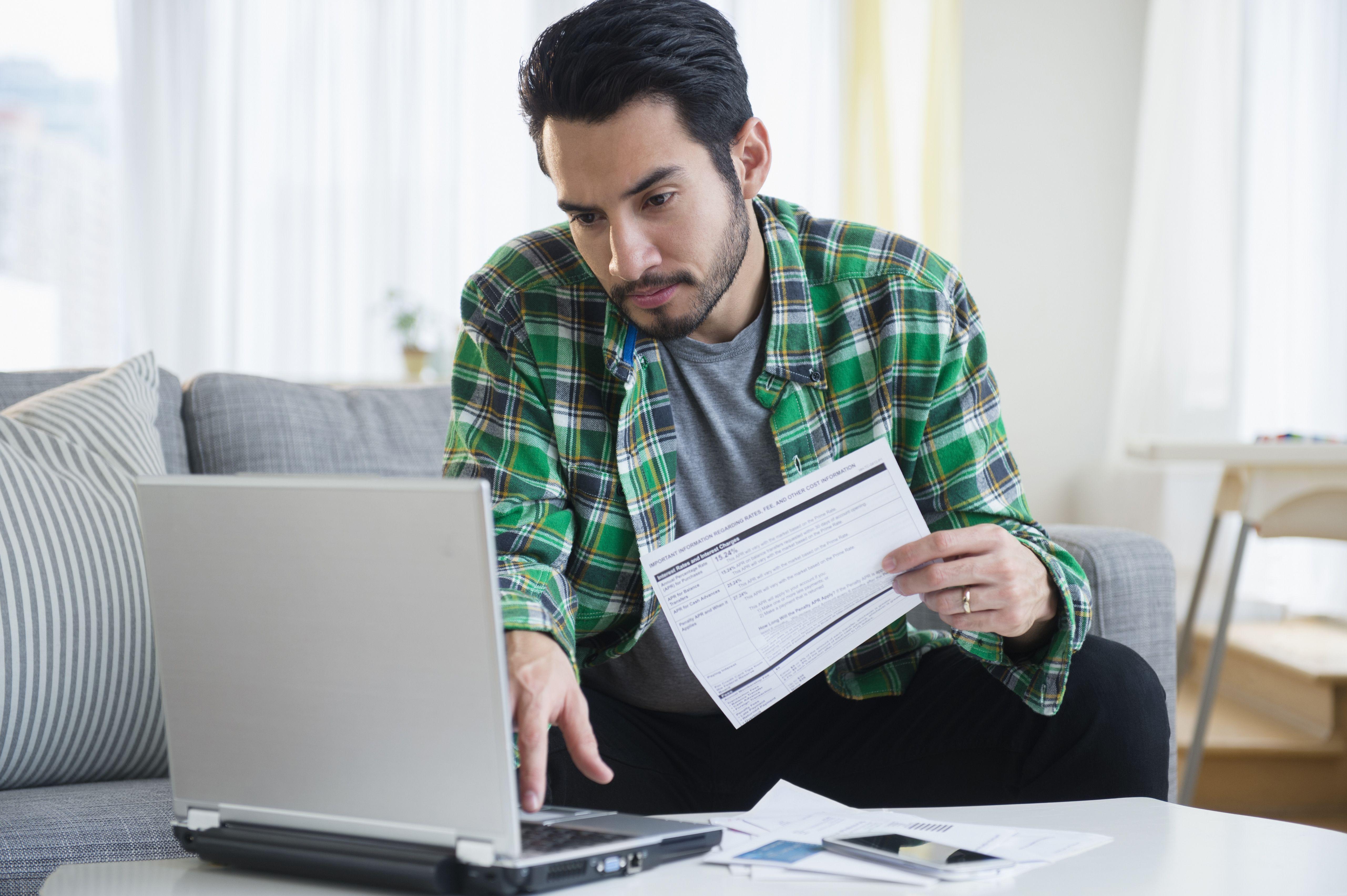 Mann, der Rechnungen im Wohnzimmer bezahlt