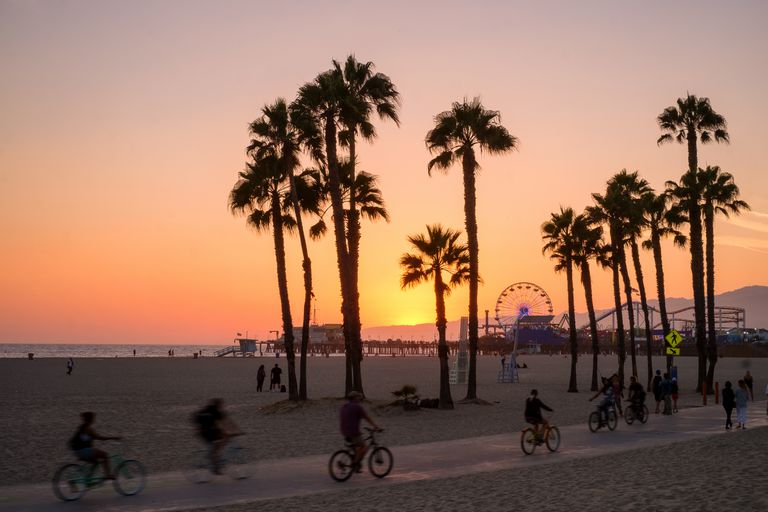 People ride bikes and walk along the beach at sunset in Santa Monica, California.