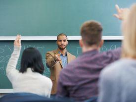 students raising their hands in a math class