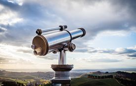 telescope over a landscape and cloudy sky