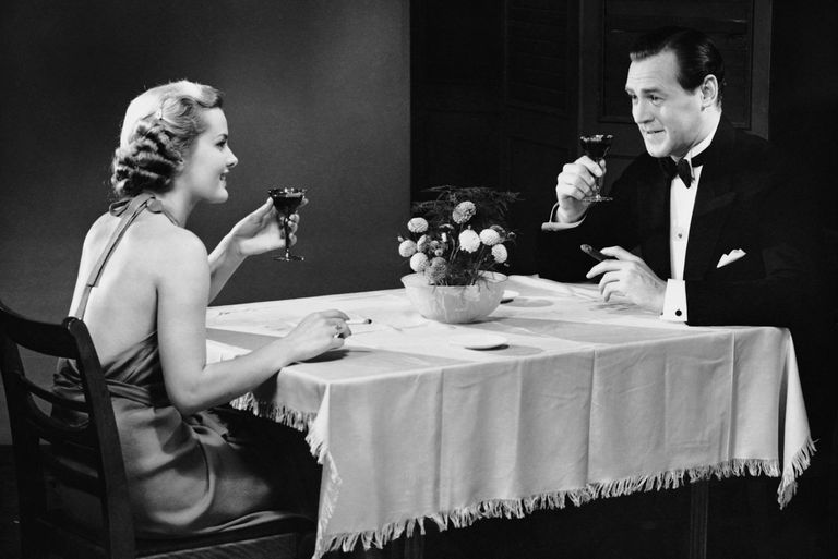 Couple sitting at a table, smoking and drinking, circa 1950s