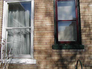 λεπτομέρεια από άβαφο λευκό παράθυρο δίπλα σε ένα βαμμένο κόκκινο παράθυρο
