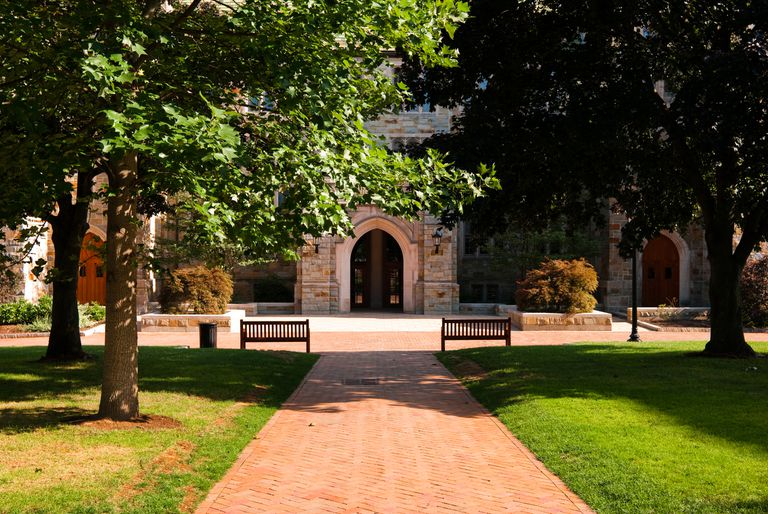 """""""A brick walkway surrounded by green grass leading up towards an educational building at Boston College in Chestnut Hill, MA."""