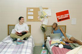 Male college students smiling at each in dorm room