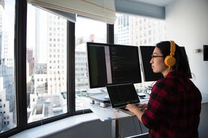Programmer at a desk with multiple monitors overlooking a city scene