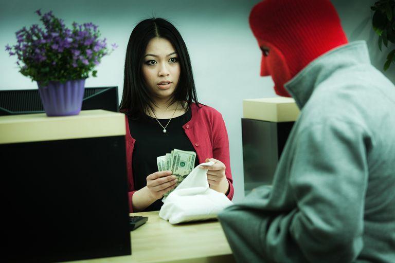 Female Bank Teller Giving a Robber Money