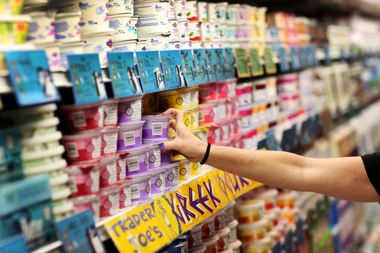 Woman selects yogurt from grocery store