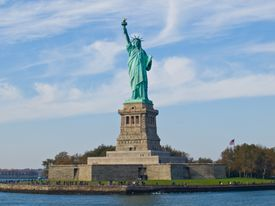 Statue of Liberty on a sunny day with tourists all around.