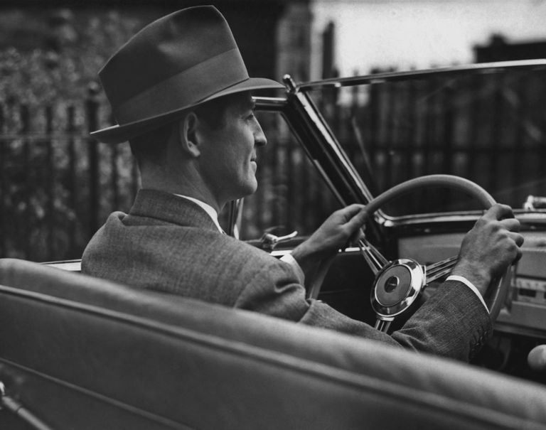 black and white photo of a man behind the wheel of a 1940s car