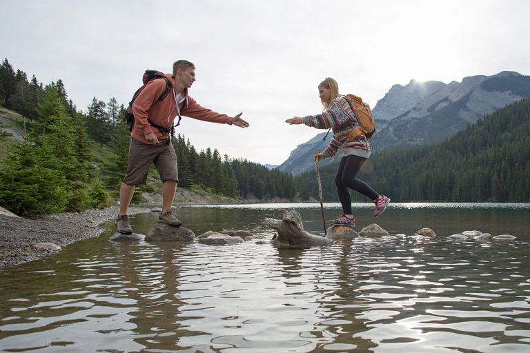 Man offering helping hand to friend while hiking