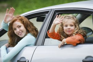 woman and child leaning out of car windows waving