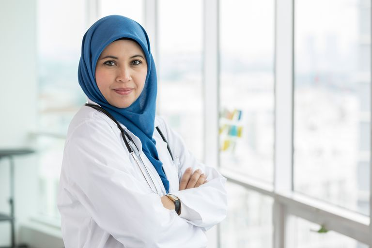 Muslim doctor stands in front of window