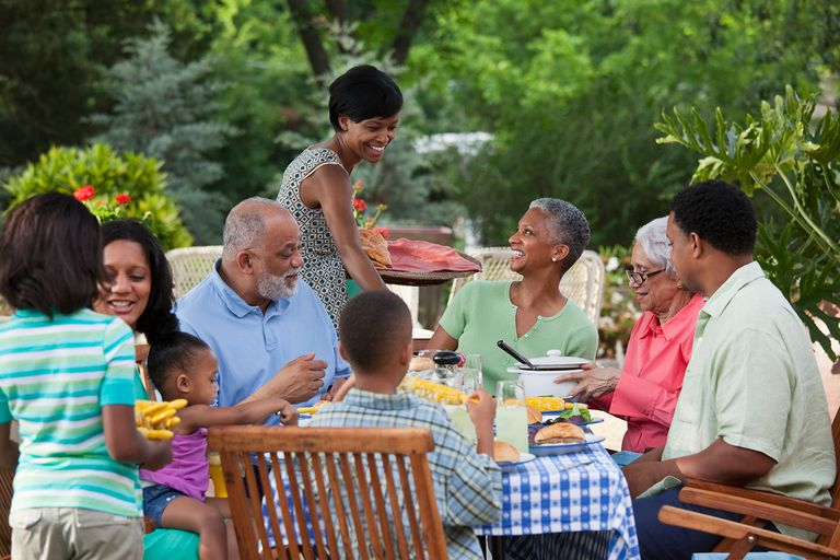 Multi-generation Black family eating at barbecue in back yard.