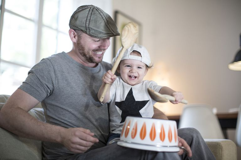 baby banging wooden spoons on bowl with dad